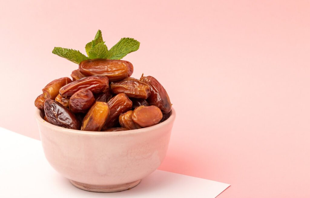 a pink bowl with whole dates inside garnished with mint