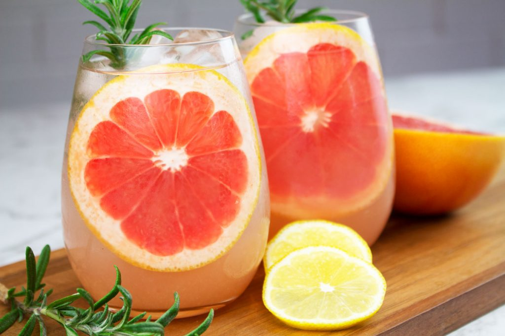 grapefruit mocktail recipe in 2 round glasses garnished with big slices of grapefruit and a sprig of rosemary