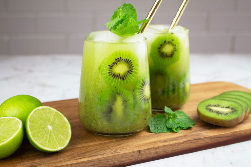 mocktail recipes kiwi in 2 glasses with gold straws and slices of lime and kiwi nearby