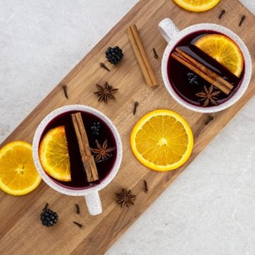 non alcoholic mulled wine flat lay looking down on 2 white mugs with orange slices, cinnamon sticks and mulled wine inside