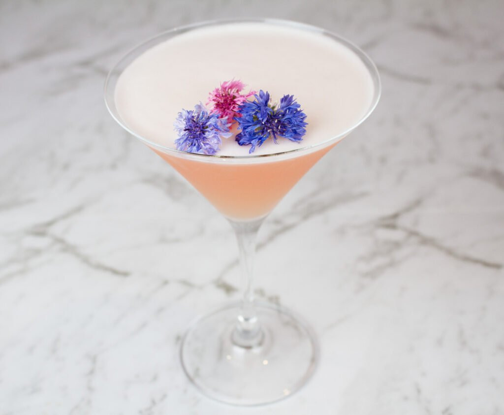 pink grapefruit martino in martini glass garnished with purple and pink flowers