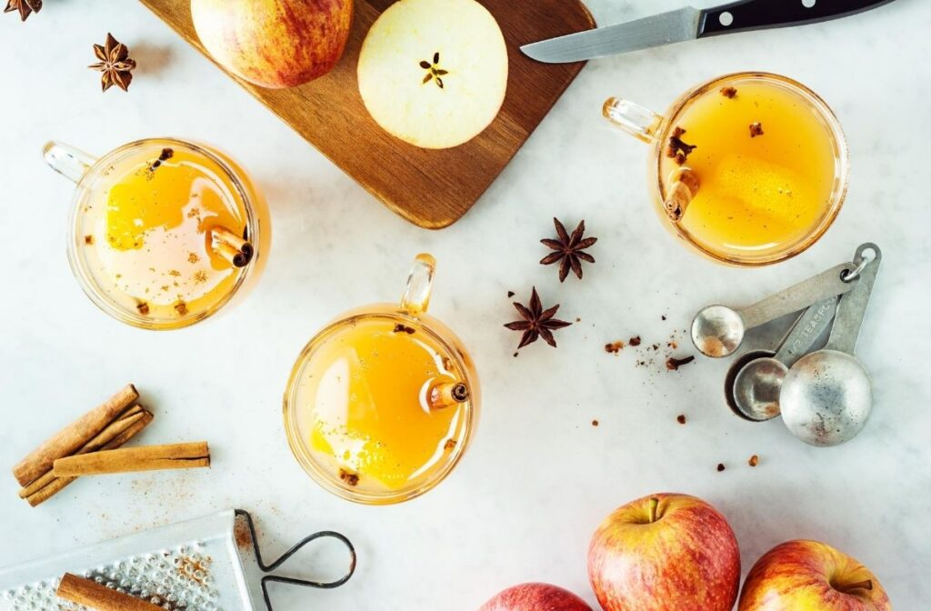 hot apple cider recipe flat lay with 3 glasses of apple cider and a bench scattered with star anise, cinnamon and apples