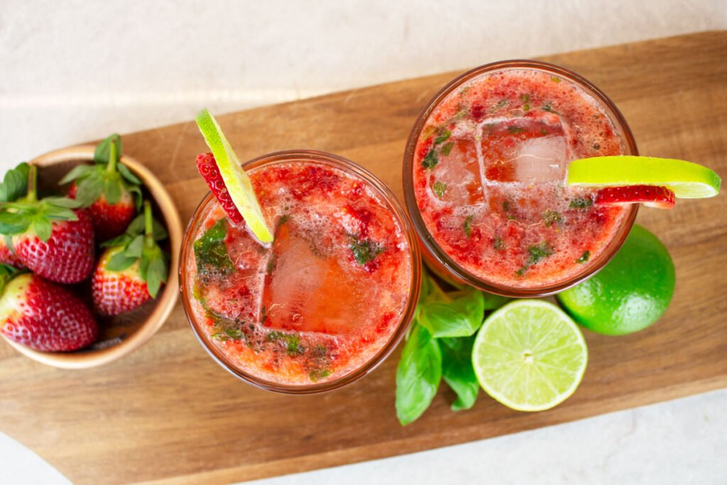 birdseye view of 2 strawberry basil mocktails garnished with slices of strawberry and lime wheels, sitting on a wooden chopping board