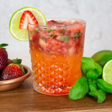 Strawberry Basil Mocktail on a wooden background with a plate of strawberries in the background