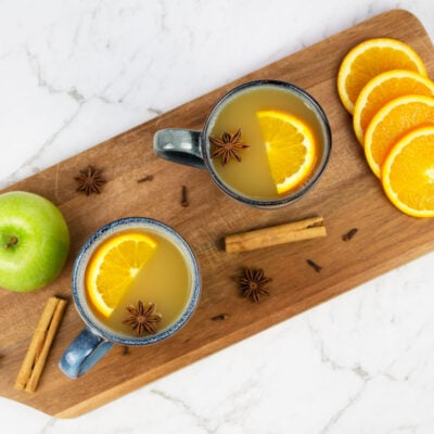 mulled apple cider flay lay with 2 blue mugs of cider garnished with orange slices and star anise