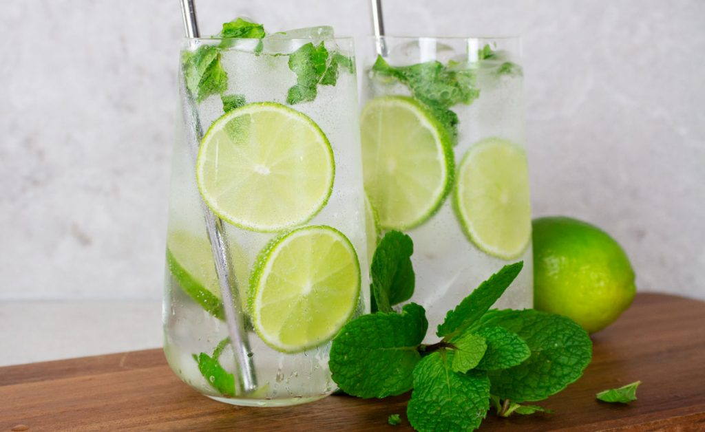 2 virgin mojitos in tall glasses garnished with lime wheels, fresh mint and silver straws