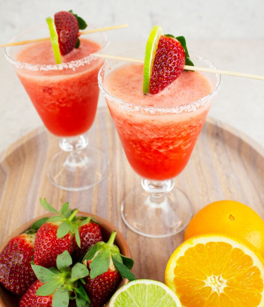 2 virgin strawberry daiquiris on a marble tray garnished with strawberry and lime