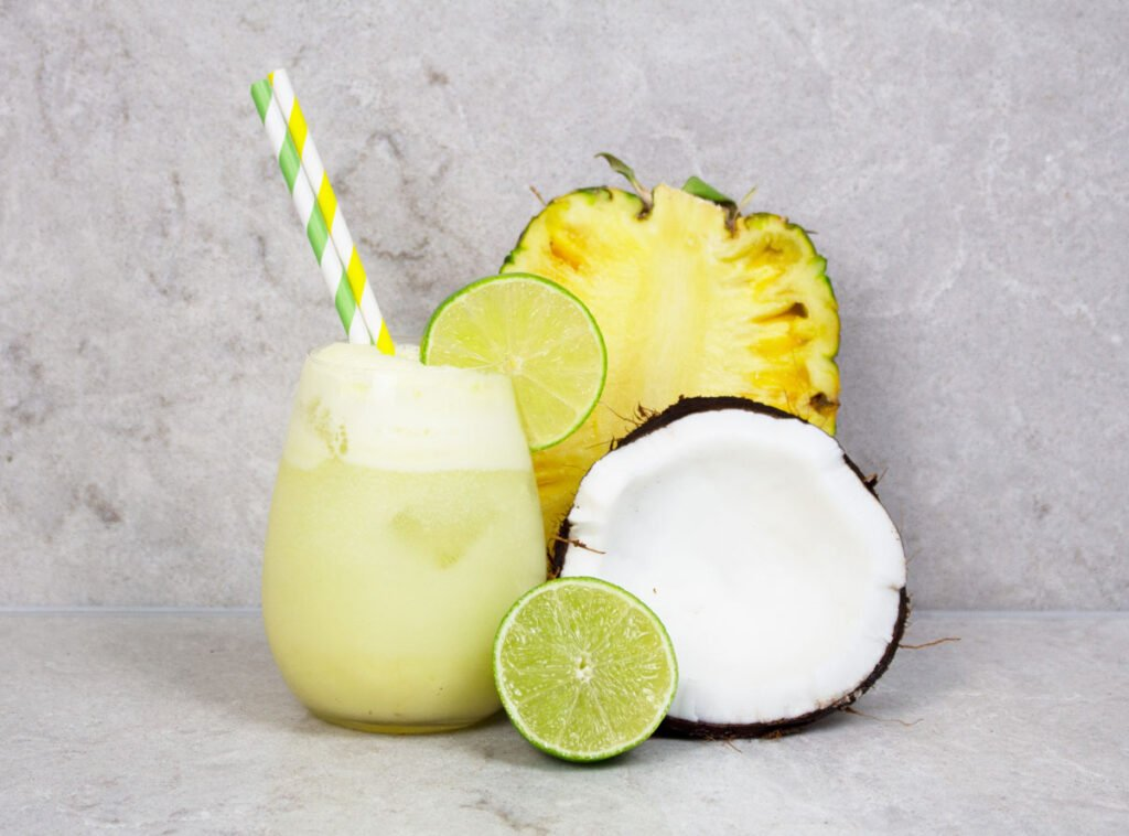 pineapple mocktail recipe with 2 green and yellow striped straws on a grey background with half pineapple, lime and coconut nearby
