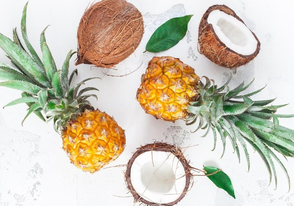 2 whole pineapples and half coconuts in a flaylay image with a white marble background