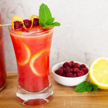 raspberry red lemonade drink garnished with lemon rind, raspberries and mint with a bowl of raspberries, lemon wheels and mint sitting nearby