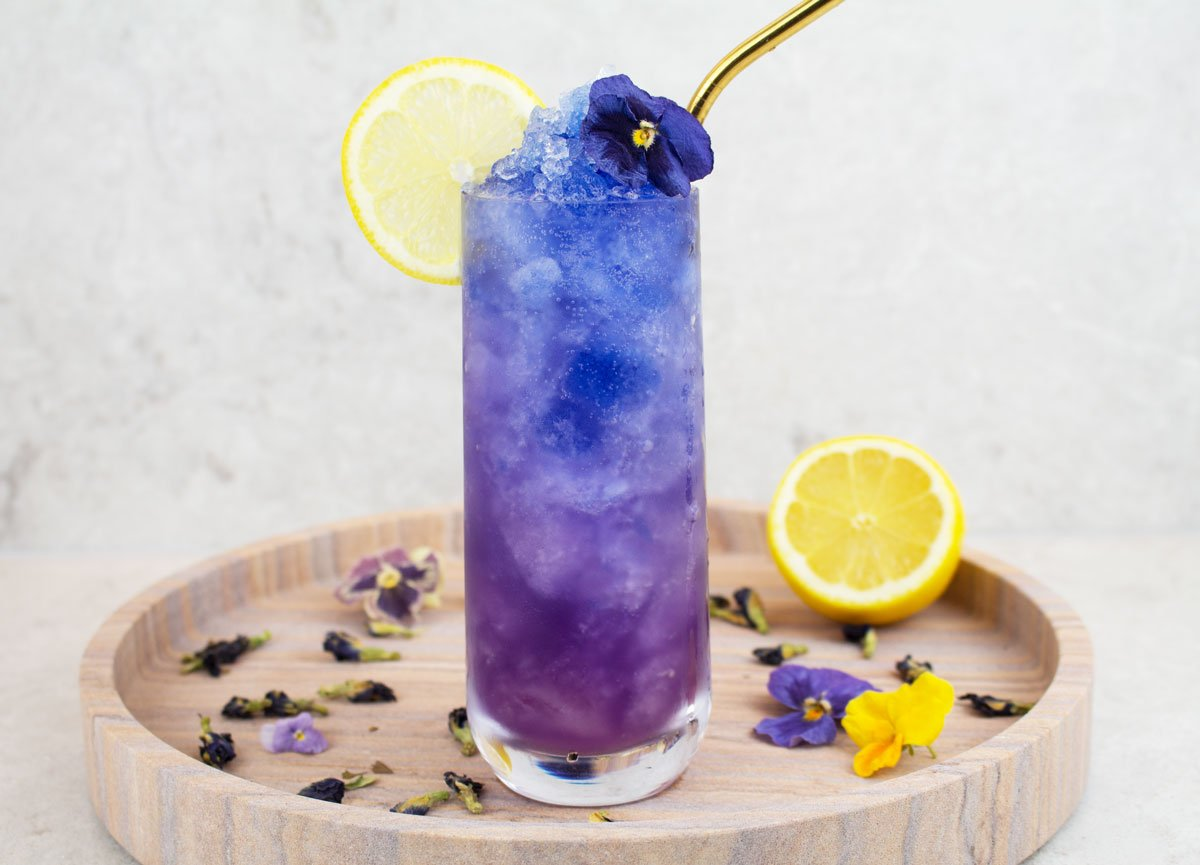 blue mocktail recipe image with a blue and purple icy drink in a tall glass with a lemon wheel and blue flower garnish and gold straw