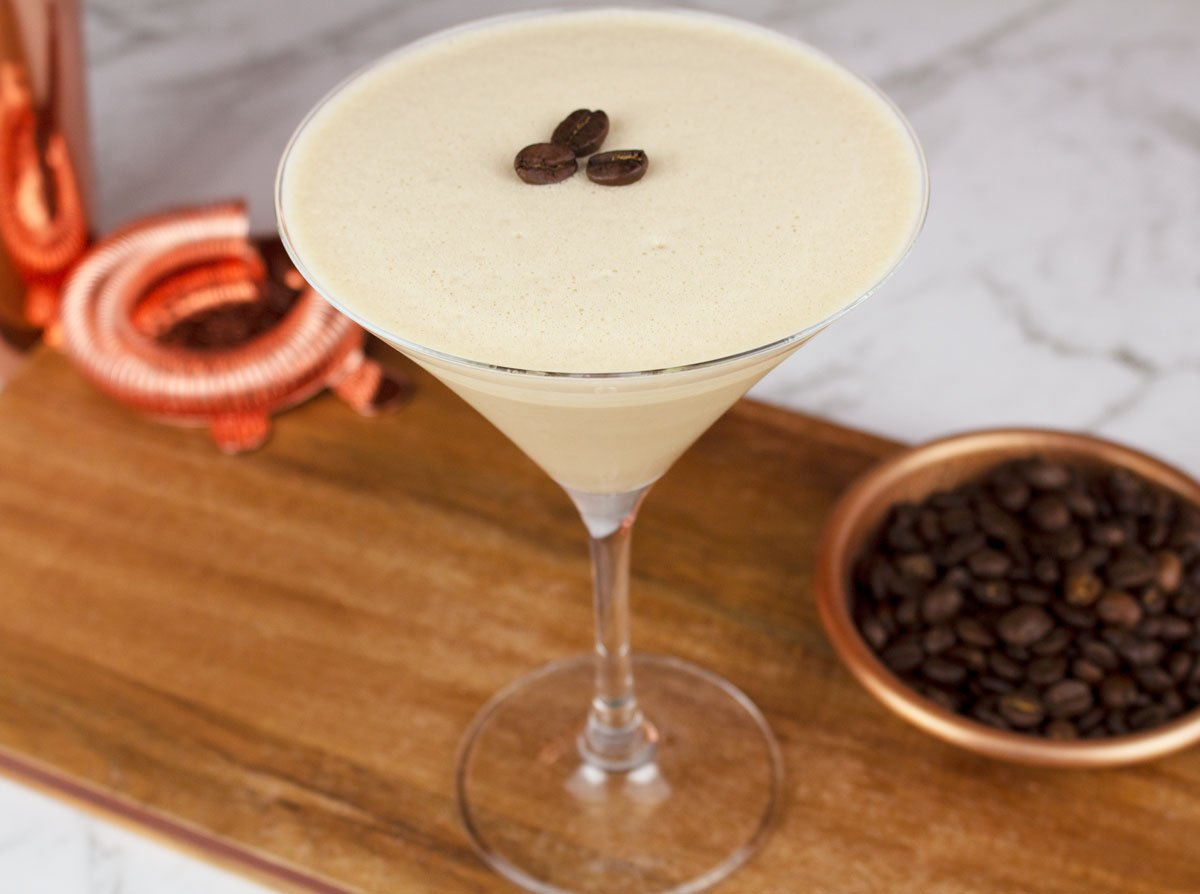 non-alcoholic espresso martini garnished with 3 coffee beans sitting on a wooden board