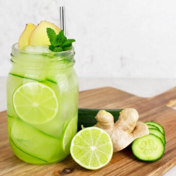 ginger mojito mocktail in a glass jar garnished with cucumber ribbons, lime wheels and a silver straw