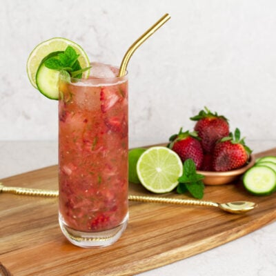 strawberry mocktail recipe in a tall glass garnished with a lime and cucumber wheel, mint and a gold straw