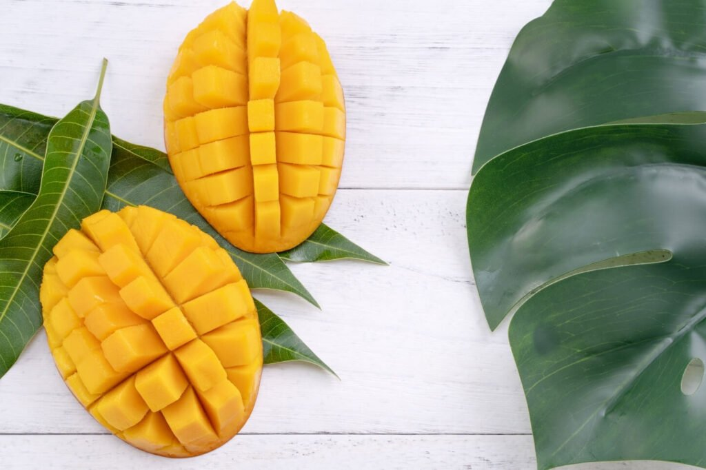 flat lay photo with sliced mango pieces and large green leaves on a white wooden look background