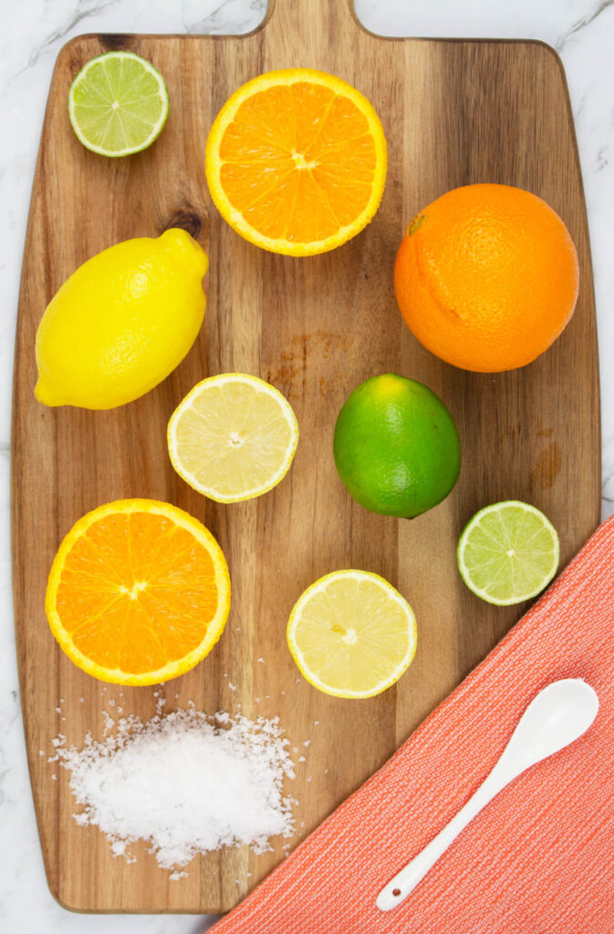 lemon, lime and orange citrus salts on a wooden chopping board with an orange tea towel and white spoon