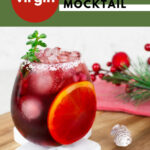 red Christmas mocktail in a round glass with ice and an orange slice with Christmas decorations in the background
