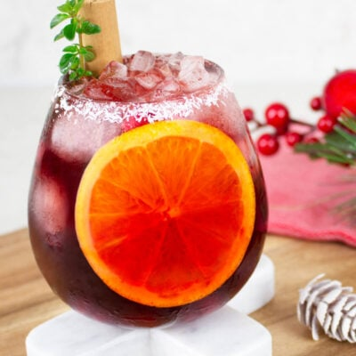 Christmas mocktail in a round glass with a coconut rim and sliced orange inside