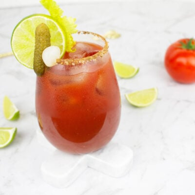 Virgin Mary mocktail on a white background garnished with lime, celery, pickle and ice.