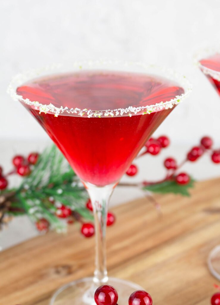 Red Virgin Cosmopolitan drink in classic martini glass that is rimmed with sugar and lime rind with Christmas decorations in the background