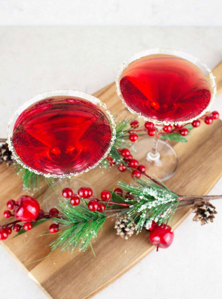 2 red cranberry mocktails in martini glasses rimmed with sugar and lime, sitting on a wooden board with Christmas decorations