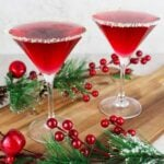 2 red mocktails in martini glasses rimmed with salt and lime on a wooden board with Christmas decorations
