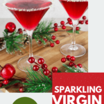2 red Christmas mocktails in martini glasses with a lime and sugar rim