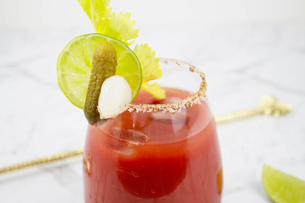 Virgin Mary drink garnished with a celery salt rim and celery, lime wheel, small pickle and pickled onion in a round glass.