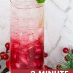 red and white christmas mocktail in a tall lass garnished with mint and a gold straw
