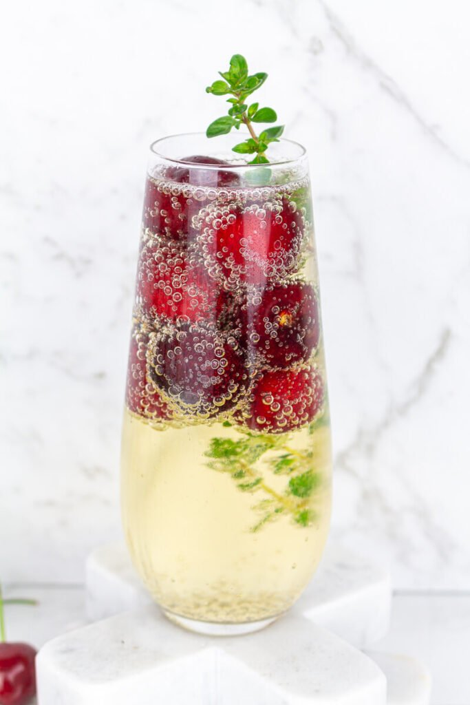 Stemless champagne glass filled with sparkling wine frozen cherries and thyme