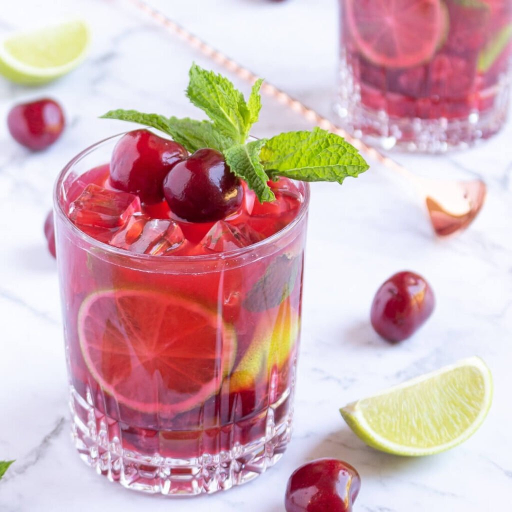 cherry mojito mocktail in a short glass garnished with cherries and mint with scattered lime wedges and cherry