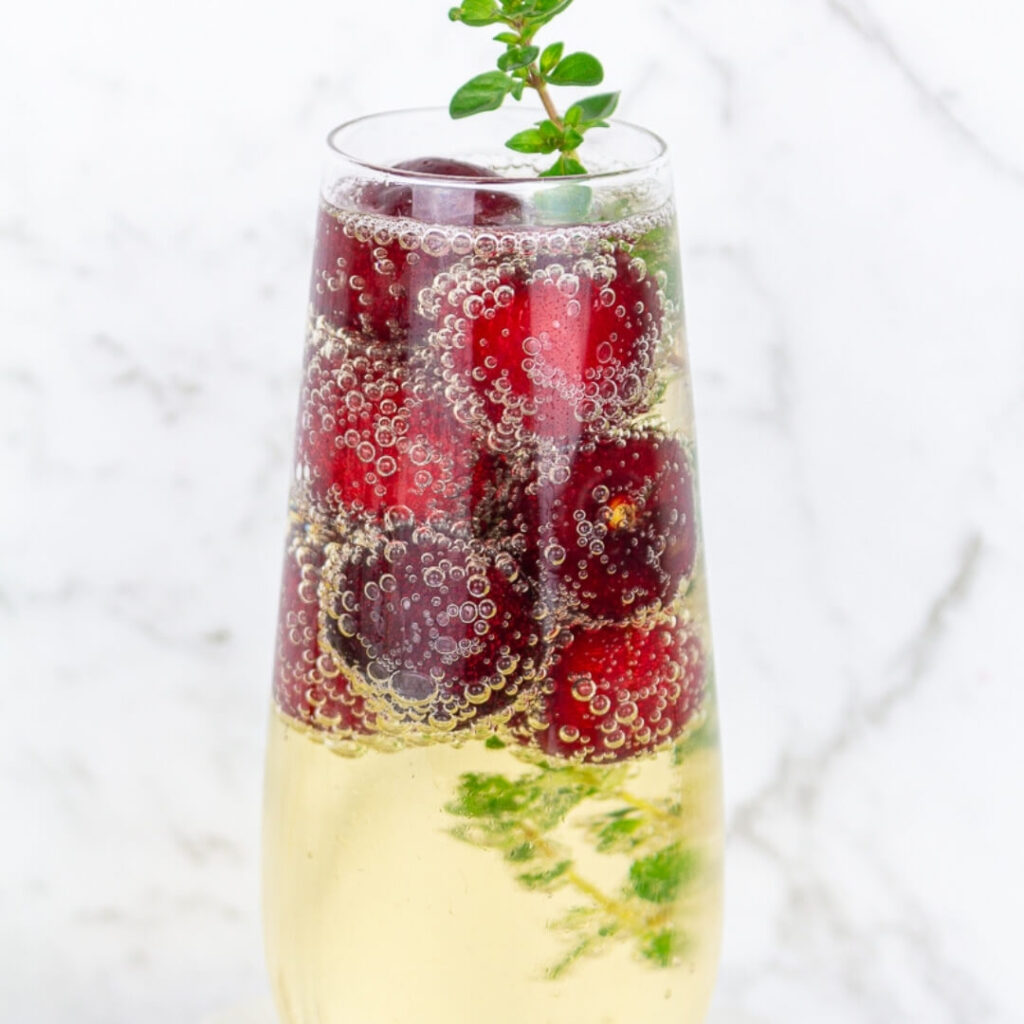 a glass of sparkling wine with an easy garnish using frozen cherries and a sprig of thyme