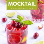 cherry mocktails in 2 glasses garnished with mint and cherries, with scattered limes