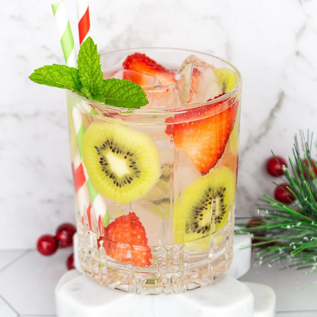 a mocktail with a garnish of strawberry and kiwi slices