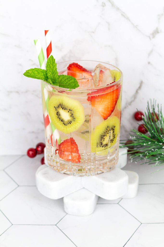 kiwi strawberry drink with ice and sparkling water with 2 red and green straws
