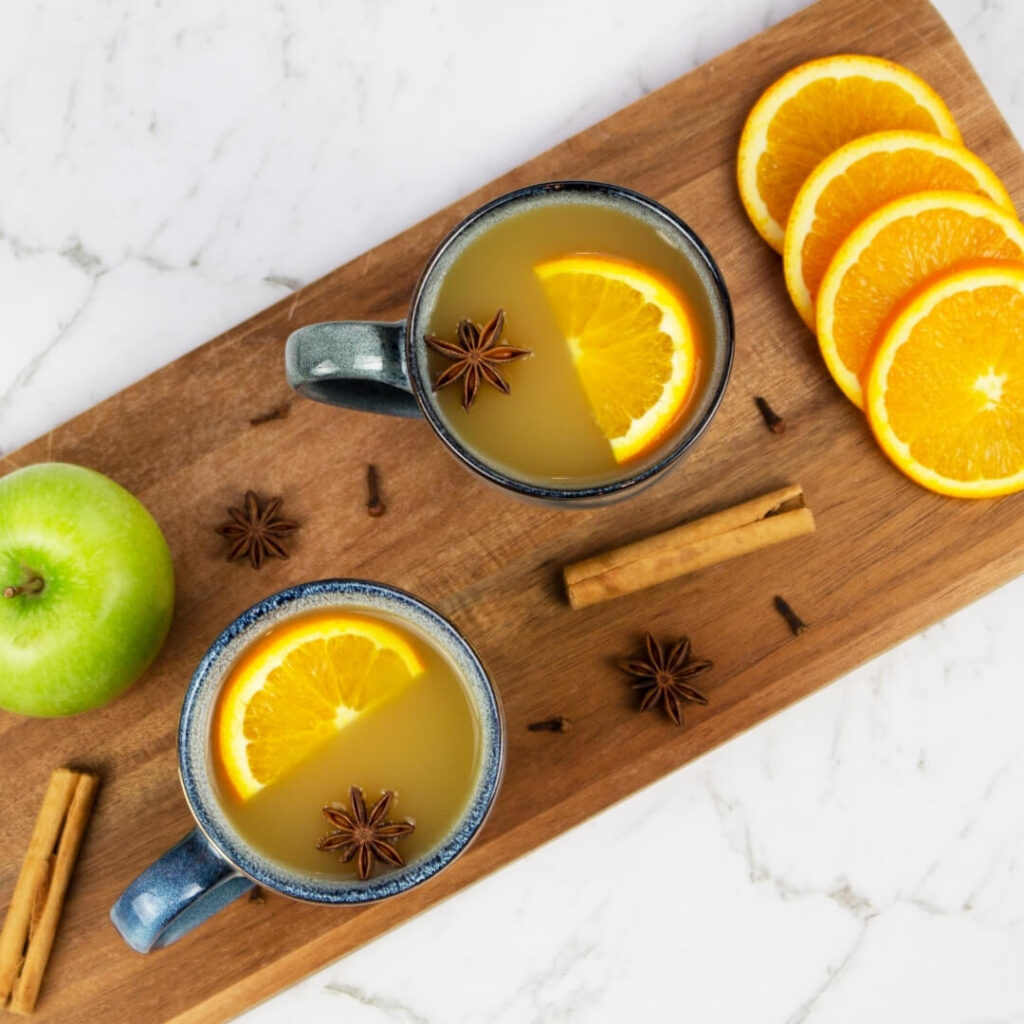 2 blue mugs of mulled apple cider on a wooden board garnished with orange slices, apple and cinnamon sticks
