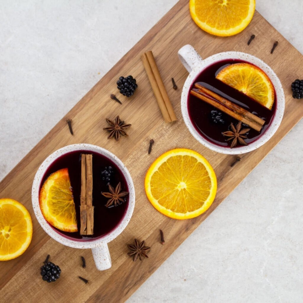 2 muds of  non alcoholic mulled wine on a wooden board garnished with orange slices and cinnamon sticks