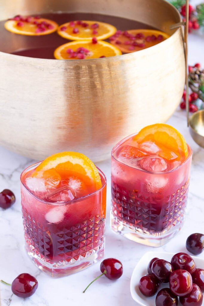 gold punch bowl with red coloured punch with 2 glasses filled with punch, ice and orange slices