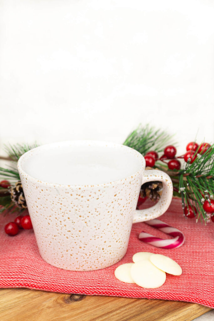 peppermint white hot chocolate on a red tea towel with white chocolate and candy canes next to it