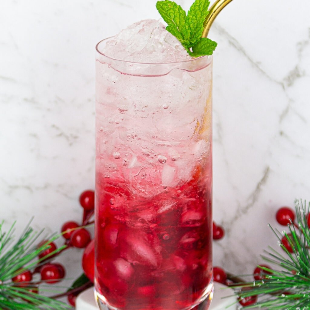 3 ingredient christmas mocktail with cranberry juice, soda and crushed ice garnished with mint and a gold straw