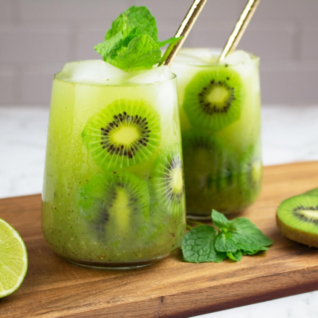 2 kiwi mocktails on a wooden board with a mint garnish and gold straws