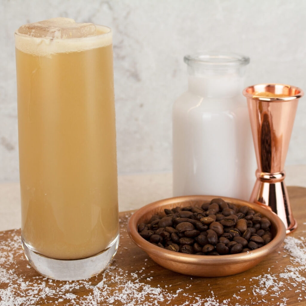 a tall glass of virgin baileys with a bowl of coffee bean and small jug of milk on a wooden board