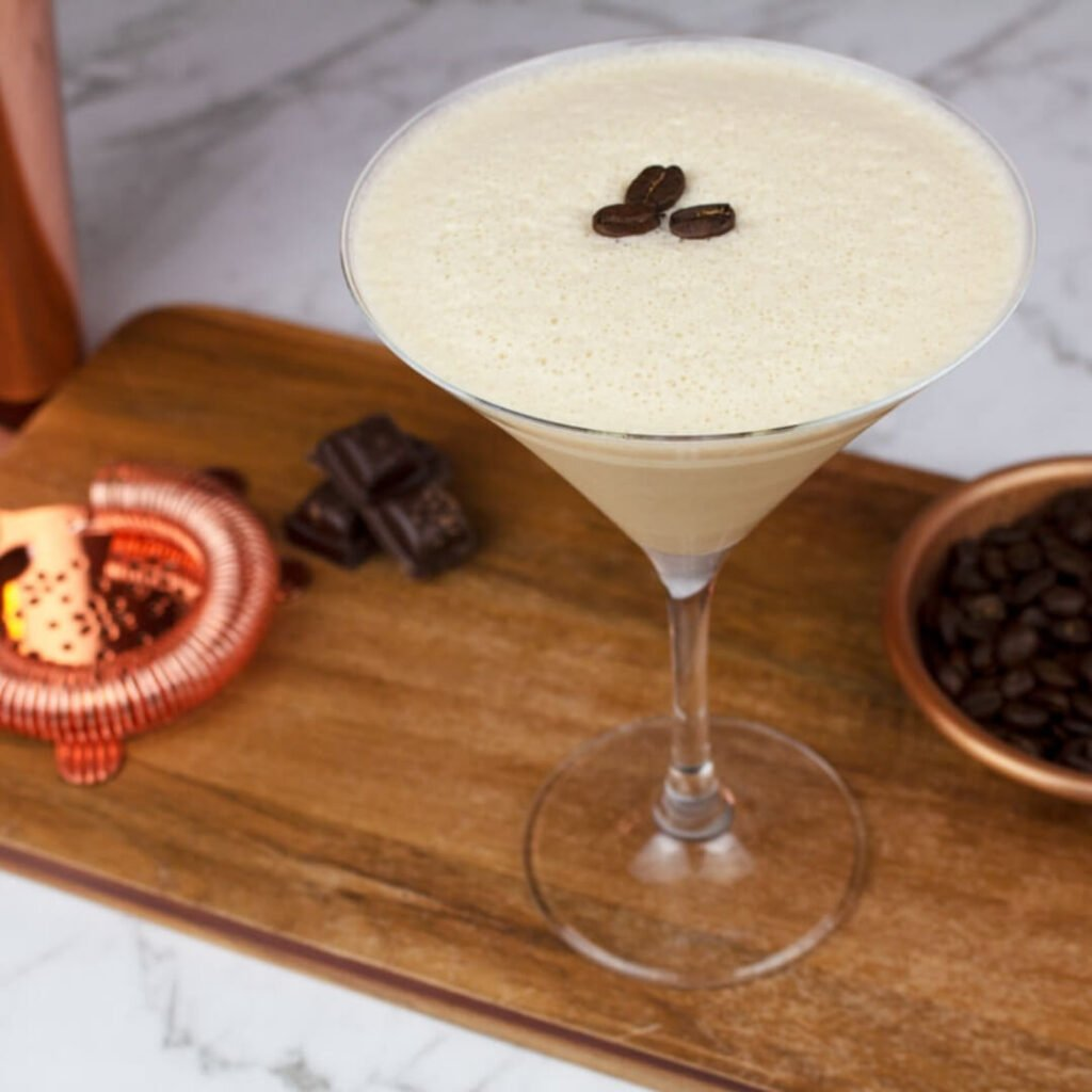a virgin espresso martini garnished with 3 coffee beans on a wooden board with chocolate and coffee beans in the background