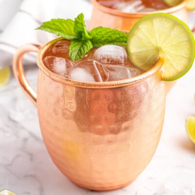 a Moscow mule mocktail in a copper glass with a lime wheel and mint as garnish on a grey and white marble bench top