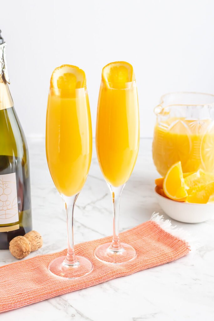 2 orange mimosa mocktails in champagne flutes with a jug of juice and orange slices
