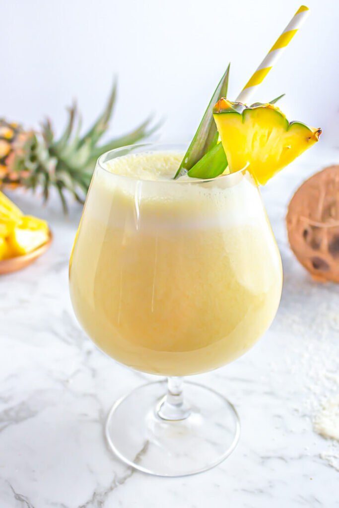 piña colada mocktail in a cocktail glass garnished with a pineapple wedge on a grey and white marble backdrop