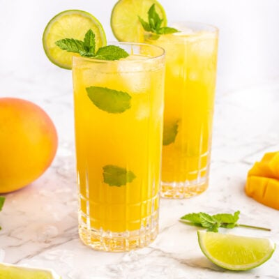 2 mango mocktails in tall glasses garnished with al lime wheel and sprig of mint on a grey and white marble background