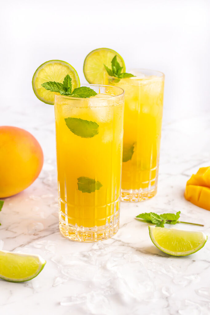 2 mango virgin mojito mocktails in tall glasses garnished with al lime wheel and sprig of mint on a grey and white marble background