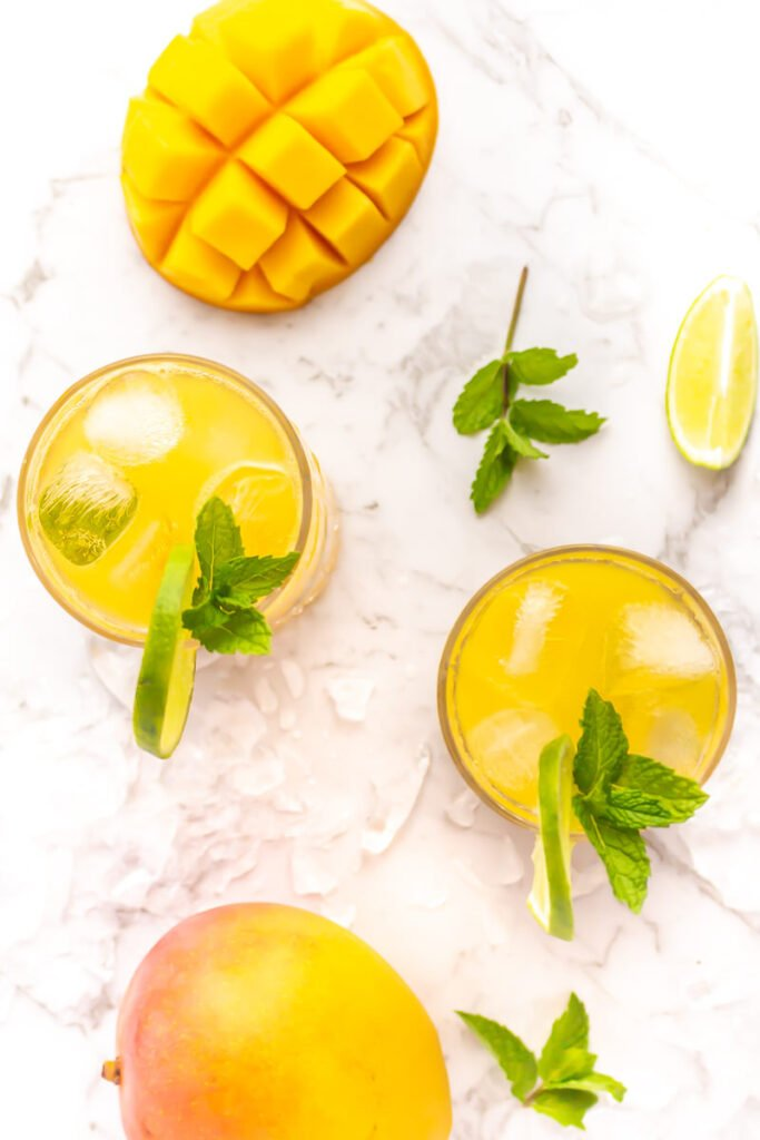 flatlay of 2 mango mojito mocktails on a grey and white marble background with fresh mango, mint, lime and ice in the background