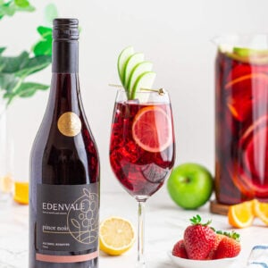 non alcoholic sangria mocktail in a wine glass garnished with an apple fan and lemon round with a jug of Sangria and a bottle of Edenvale pinot noir